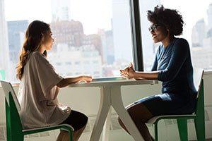 two-women-sitting-on-chairs-beside-window-1181719